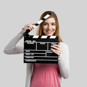 Beautiful girl holding clapboard — Stock Photo