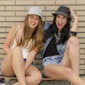 Girlfriends having fun with a skateboard — Stok fotoğraf