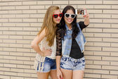 Young girlfriends taking pictures — Stock Photo