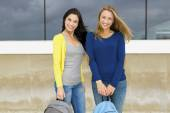 Teenage students holding backpacks and smiling — Stock Photo