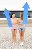 Girls holding a giant blue arrows — Stock Photo