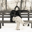 Young man in casual clothes sitting on winter bench  — Stock Photo #59024025