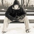 Young man in casual clothes sitting on winter bench  — Stock Photo #59024027
