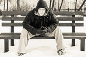 Young man in casual clothes sitting on winter bench  — Stock Photo