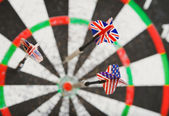Old perforation dartboard with flags on darts — Stock Photo