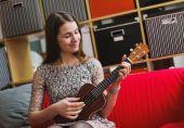 Young beauty woman playing on ukelele — Stock Photo