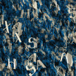 Crumple paper with many abstract blue alphabet letters — Stock Photo #73177997