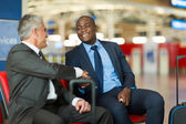 Business travellers handshaking at airport — Stock Photo