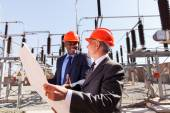 Industrial managers holding blueprint — Stock Photo