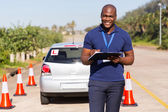 Driving instructor writing on clipboard — Stock Photo