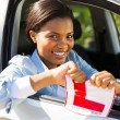 Girl in a car tearing her L sign — Stock Photo #57416541