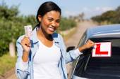 Woman removing learner driver sign — Stock Photo