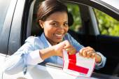 Girl in a car tearing her L sign — Stock Photo