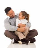 Daughter sitting on father's lap — Stock Photo
