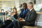 Business travelers using laptop — Stock Photo