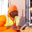 African electrician checking computerized machine status — Stock Photo #58175693
