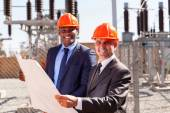 Industrial managers holding blueprint — Foto Stock