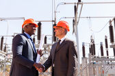 Businessmen handshaking in substation — Stock fotografie