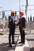 Managers handshaking in electrical substation — Foto Stock