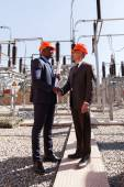Managers handshaking in elektrische onderstation — Stockfoto