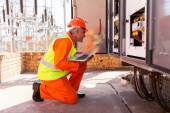 Mid age electrician kneeing in front of transformer — Stock Photo