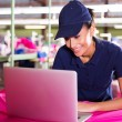 Female factory worker using laptop — Stock Photo #59683689