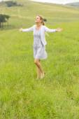 Young girl with arms outstretched on grassland — Stock Photo