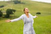 Young woman with arms open on grassland — Stock Photo