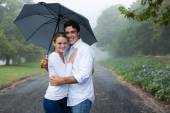 Young couple under an umbrella in the mist — Stock Photo