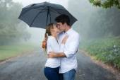 Couple kissing under an umbrella — Stock Photo