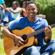 African college student playing guitar — Stock Photo #70620565