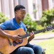 Young college student playing guitar — Stock Photo #70624543