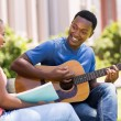 College student playing guitar for his girlfriend — Stock Photo #70625493