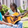 African girl playing guitar for her boyfriend — Stock Photo #70625709