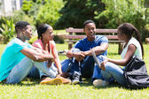 Group of university students relaxing outdoors — Stock Photo