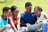 Group of university students using laptop — Stock Photo