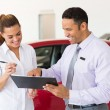 Woman buying a new car at vehicle showroom — Stock Photo #71209969