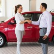Young woman handshaking with car salesman — Stock Photo #71210323