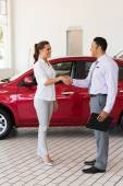 Young woman handshaking with car salesman — Stock Photo