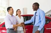 Car salesman handshaking with buyer — Stock Photo