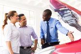 Vehicle dealer showing couple new car engine — ストック写真
