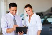 Vehicle dealership principal and saleswoman looking at clipboard — Stock Photo