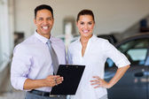 Two workers standing inside car showroom — Stock Photo