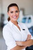 Saleswoman standing at car dealership — Stock Photo