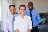 Female car dealer with colleagues on background — Stock Photo