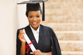 African female graduate standing outdoors — Stockfoto
