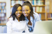 Students friends smiling in library — Stock Photo
