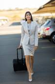 Businesswoman walking in airport parking lot — Stock Photo