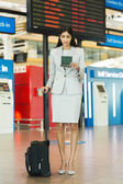 Young businesswoman with luggage at airport — Stock Photo