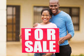 Couple with for sale sign — Stock Photo